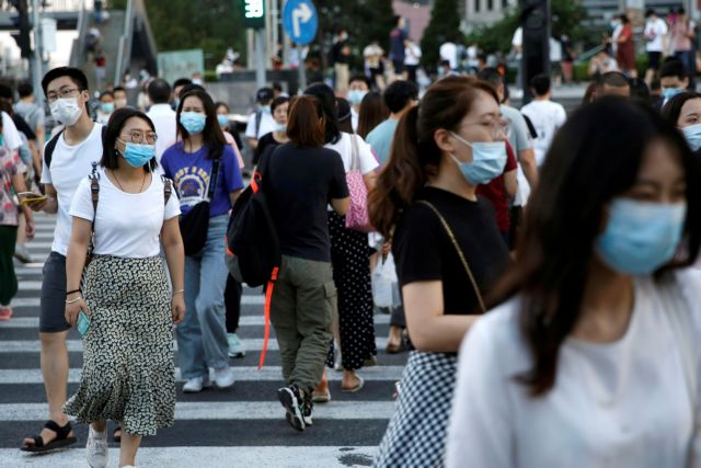FILE PHOTO: People wearing face masks following the coronavirus disease (COVID-19) outbreak walk across a street at a shopping area in Beijing, China August 25, 2020. REUTERS/Tingshu Wang/File Photo