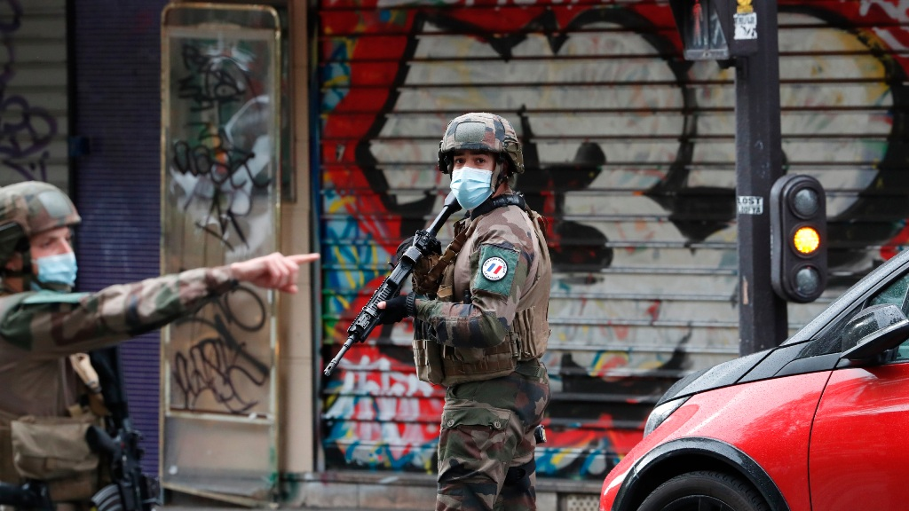 "French soldiers patrol after four people have been wounded in a knife attack near the former offices of satirical newspaper Charlie Hebdo, Friday Sept. 25, 2020 in Paris. A police official said officers are ""actively hunting"" for the perpetrators and have cordoned off the area including the former Charlie Hebdo offices after a suspect package was noticed nearby. Islamic extremists attacked the offices in 2015, killing 12 people. (AP Photo/Thibault Camus)"