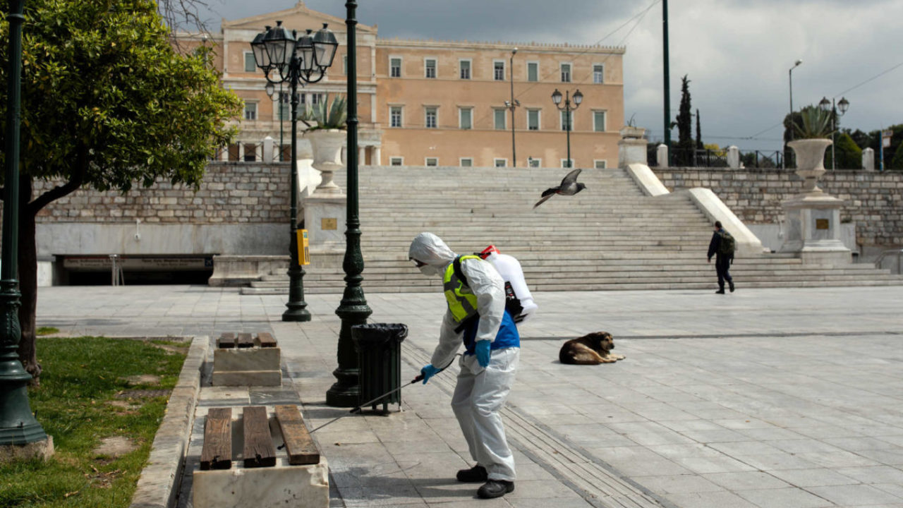 A municipal worker wearing a protective suit disinfects Syntagma square, after the Greek government imposed a nationwide lockdown to contain the spread of the coronavirus disease (COVID-19), in Athens, Greece, March 23, 2020. REUTERS/Alkis Konstantinidis