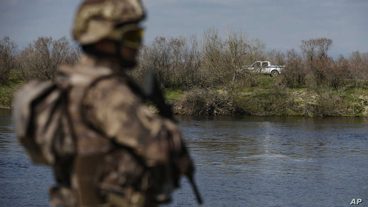 """A Greek police vehicle, background, drives past in front of a Turkish special forces team, front left, patrolling along the Maritsa river at the Turkish-Greek border near Karpuzlu village, in Edirne region, Turkey, Wednesday, March 11, 2020. Turkey's President Recep Tayyip Erdogan on Wednesday made the incendiary claim that the Greek authorities' alleged mistreatment of migrants at its border was comparable to """"what the Nazis did"""" and said he would denounce Greece's action at international platforms. (AP Photo/Emrah Gurel)"""