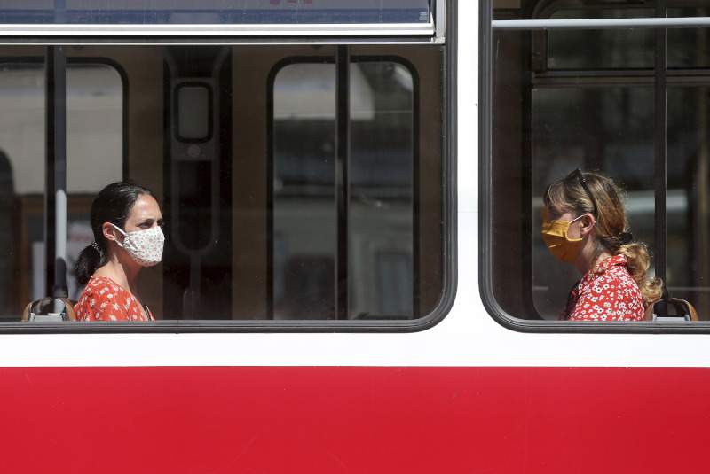 People wear face mask as they sit in a tram in Vienna, Austria, Wednesday, Aug. 19, 2020. Most people are wearing face masks in public transport to protect against the spread of COVID-19 coronavirus. (AP Photo/Ronald Zak)