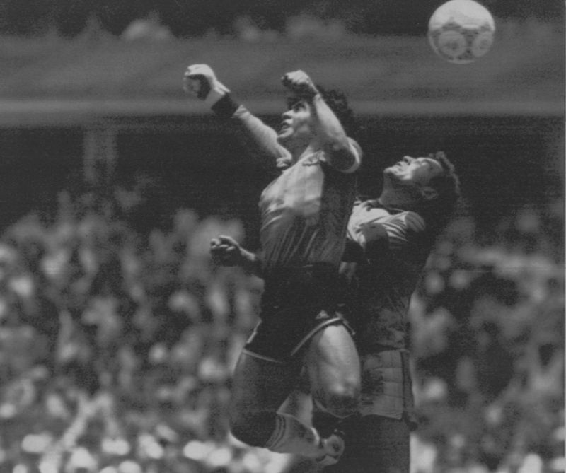 "** FILE ** Argentina's Diego Maradona, left, beats England goalkeeper Peter Shilton to a high ball and score his first of two goals in a World Cup quarterfinal in Mexico City, in this June 22, 1986 photo. Argentina won 2-1. Maradona acknowledged that he struck the ball with his hand in the famous ""Hand of God"" goal against England in the 1986 World Cup quarterfinals.  Speaking on his local television talk show Monday night, Aug. 22, 2005, Maradona called one of soccer's most controversial goals ""something that just came out of me. It was a bit of mischief."" (AP Photo/El Grafico, Buenos Aires)"
