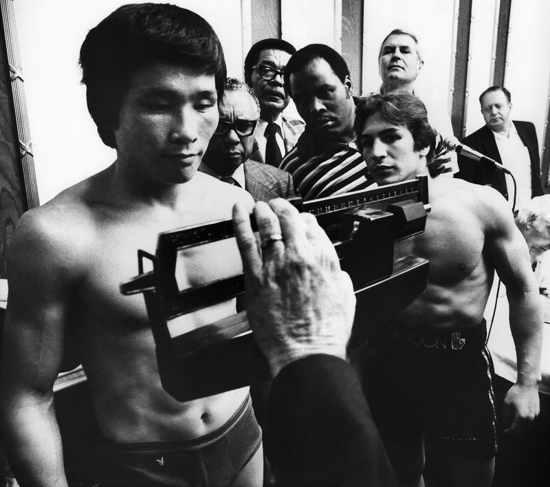 "WBA Lightweight champion Ray ""Boom Boom"" Mancini, right, watches as challenger Duo Koo Kim of Korea stands on the scale during the weigh-in for their championship fight in Las Vegas on Nov. 12, 1982. (AP Photo/Scott Henry)"