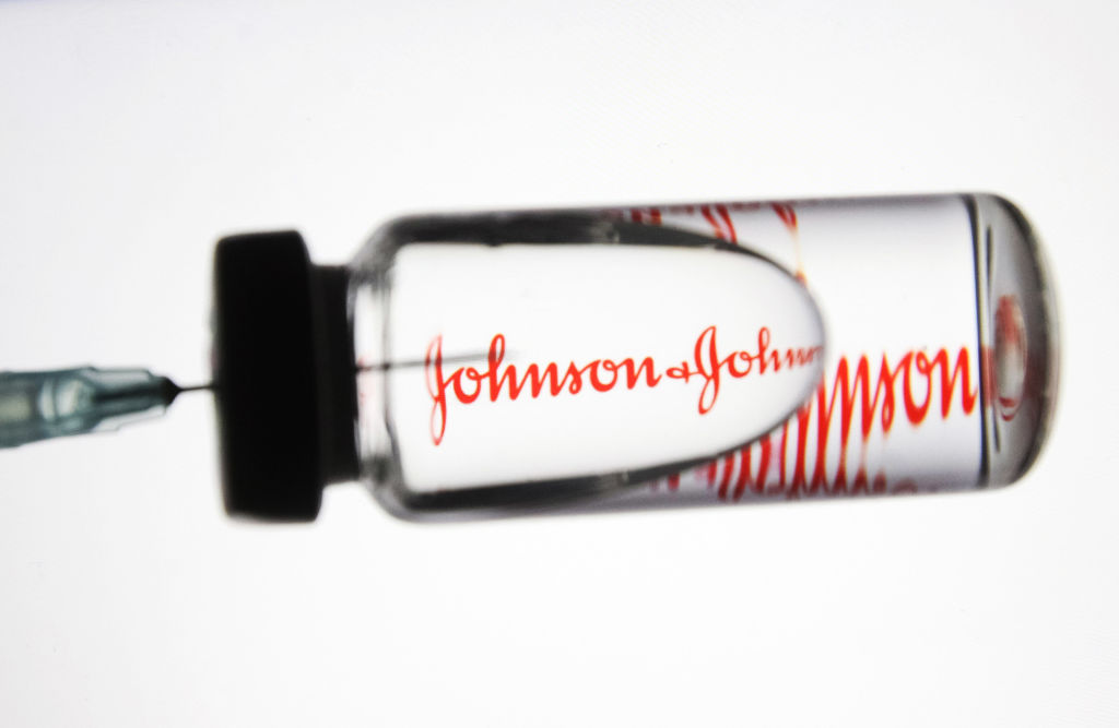 UKRAINE - 2020/11/24: In this photo illustration a medical syringe and a vial with fake coronavirus vaccine seen in front of the Johnson & Johnson logo. (Photo Illustration by Pavlo Gonchar/SOPA Images/LightRocket via Getty Images)