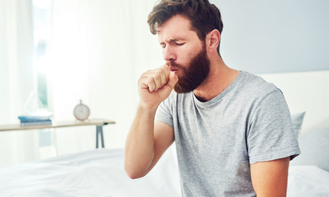 Cropped shot of a young man coughing at home