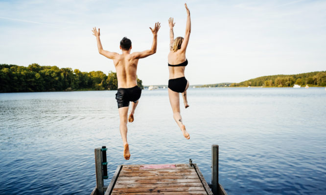Happy couple jumping into the water from a jetty